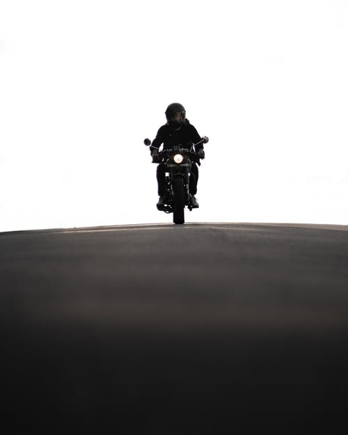 Man Riding Motorcycle on Gray Asphalt Road