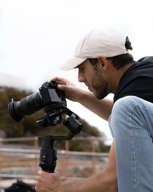 Man in Black Shirt and Blue Denim Jeans Holding Black Dslr Camera