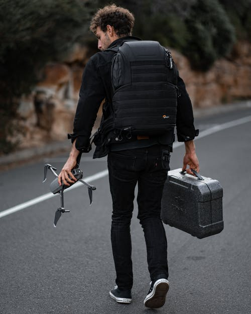 Man in Black Jacket and Black Pants Carrying Black and Gray Luggage Bag