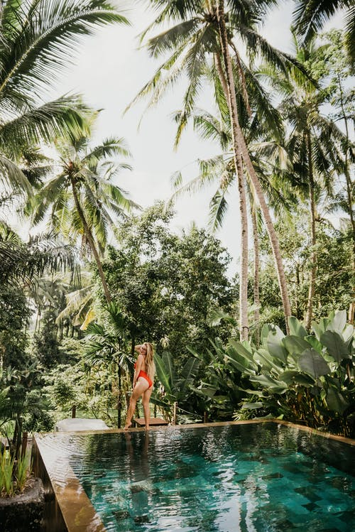 Woman in Red Dress Standing on Concrete Stairs Surrounded by Palm Trees