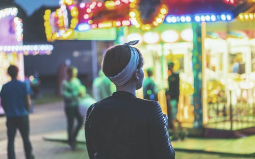 Woman Standing in Front of Carousel