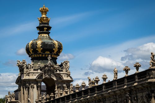 From below of crown gate of ancient Baroque styled Zwinger palatial complex with ornamental details and sculptures located against cloudy blue sky in Dresden