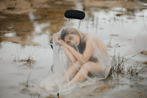 Melancholic Asian woman in veil leaning on chair in water