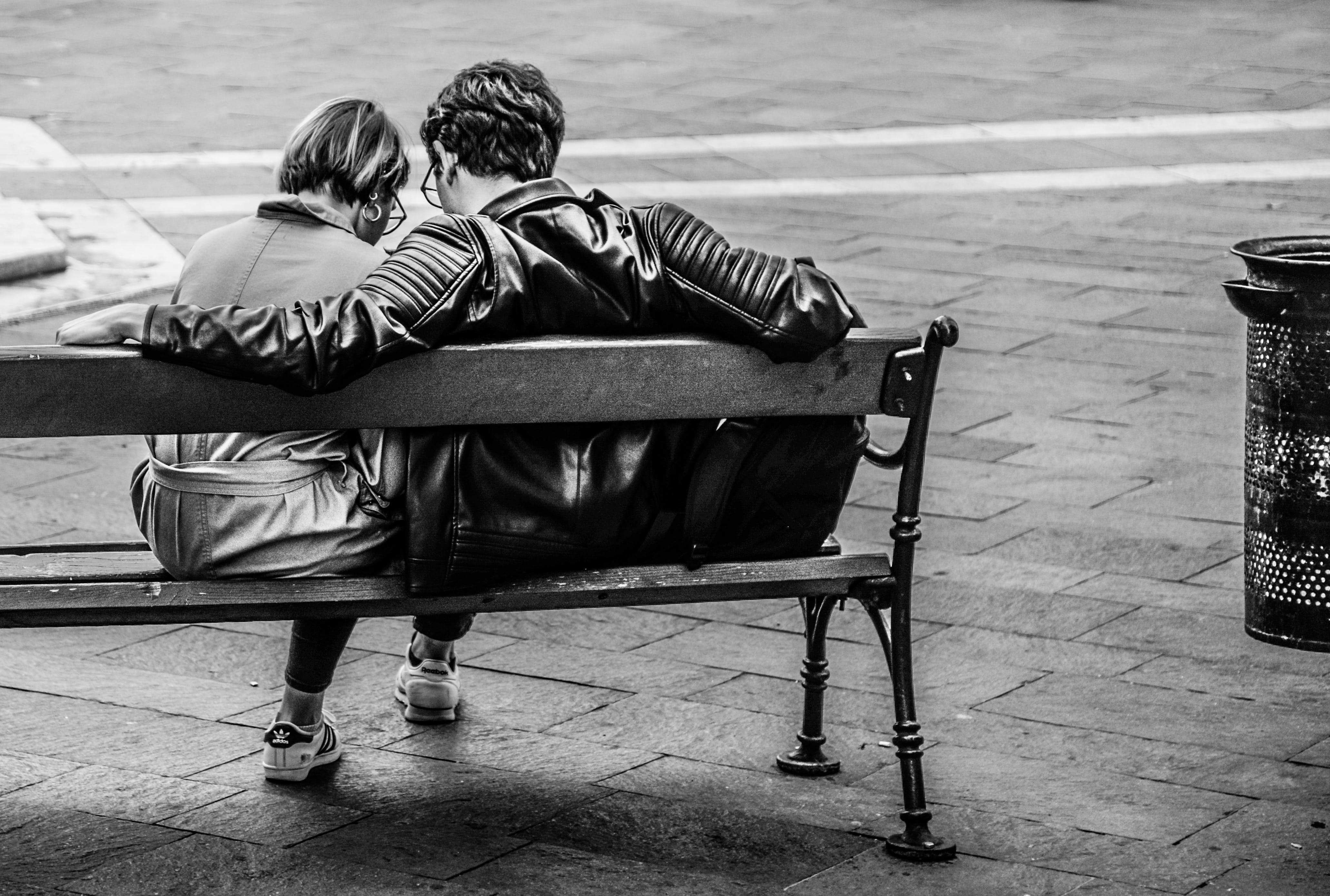 Grayscale Photo of Two Person Sitting on a Bench