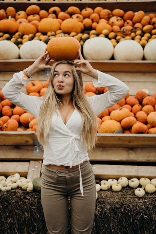 Woman in White Shirt and Blue Denim Shorts Holding Orange Fruit