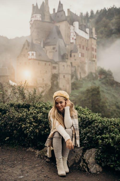 Woman Sitting on a Rock Near a Castle