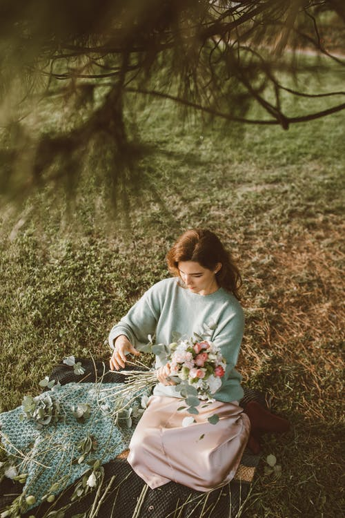 Woman in White Long Sleeve Shirt and Red Skirt Sitting on Ground With Flowers