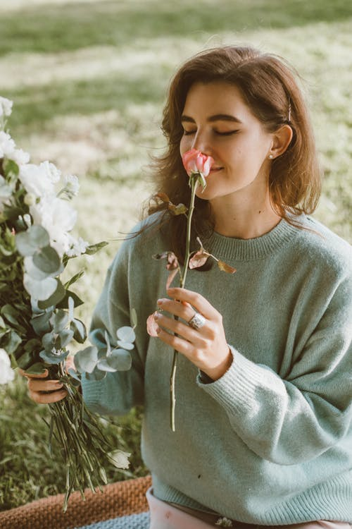 Woman in Sweater Smelling Pink Flower