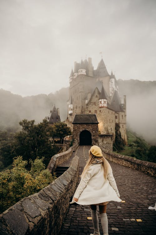 Woman in White Robe Standing on Brown Concrete Pathway Near Castle