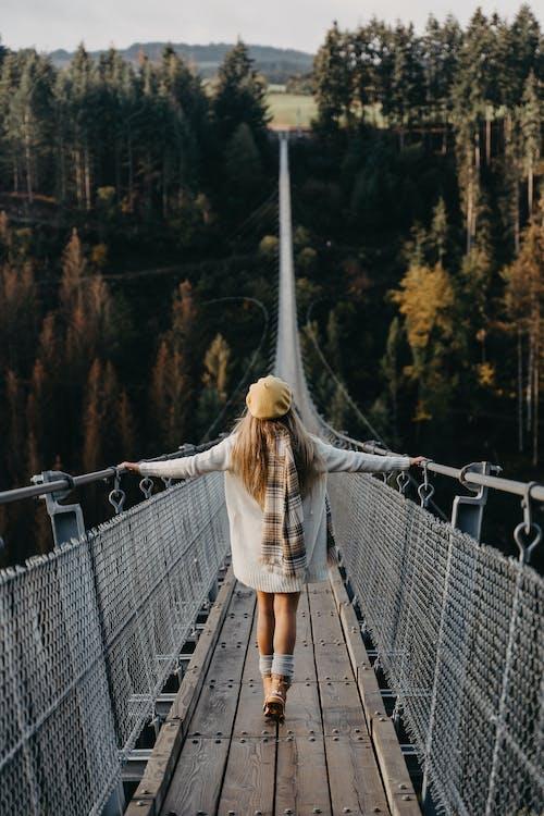 Woman in White Long Sleeve Shirt Standing on Bridge
