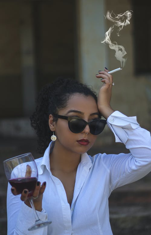 Woman in White Dress Shirt Wearing Black Sunglasses Holding Clear Drinking Glass