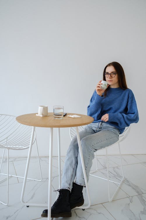 Relaxed woman with hot drink in armchair