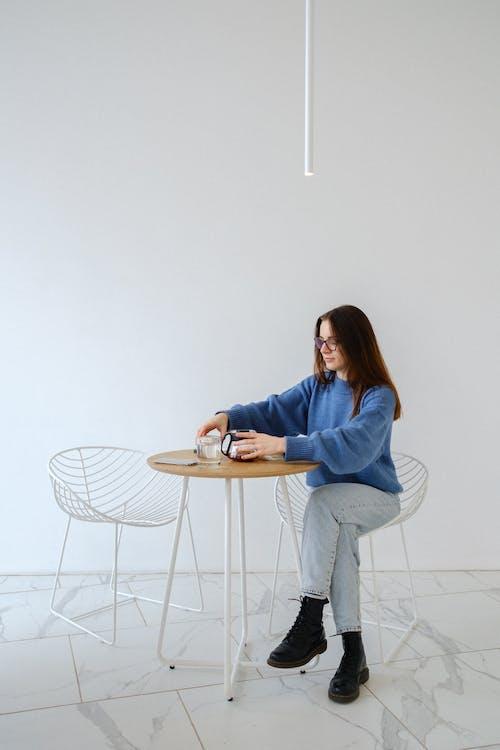 Wanita Dengan Teko Di Meja Dengan Latar Belakang Terang