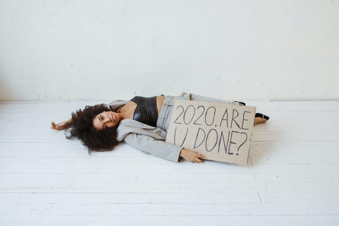 Woman in Gray Long Sleeve Shirt Lying on White Floor