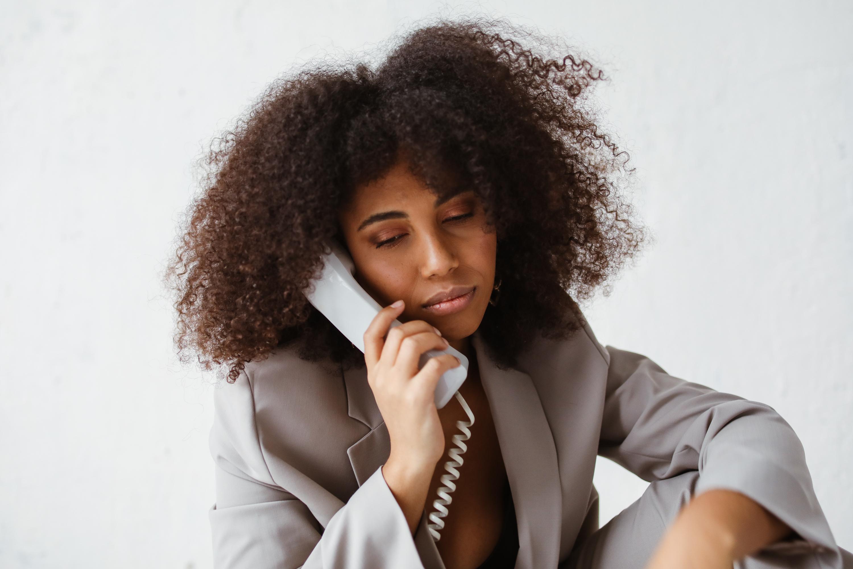 woman in white blazer holding telephone