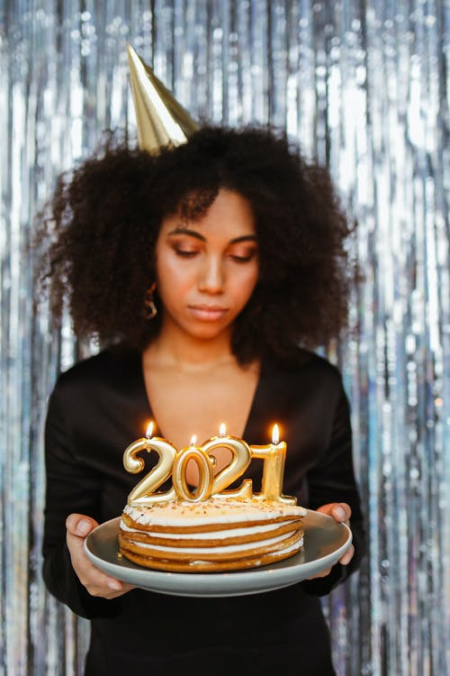 Woman in Black Shirt Holding Brown Round Cake With Lighted Candles