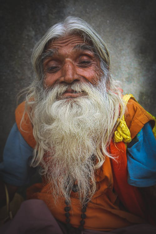 Friendly senior Indian male with wrinkled skin and gray beard looking at camera in daylight