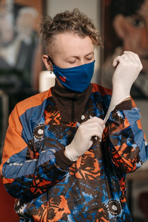 Man Wearing Face Mask and Jacket Putting On Latex Gloves