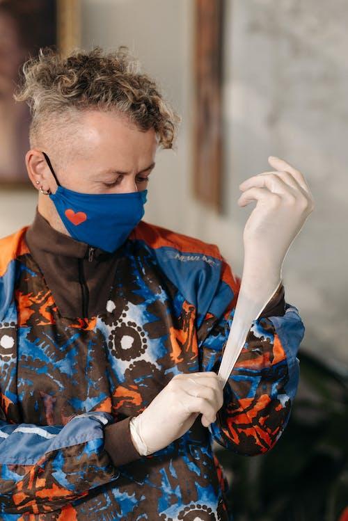 Man in Orange and Blue Jacket Wearing Latex Gloves
