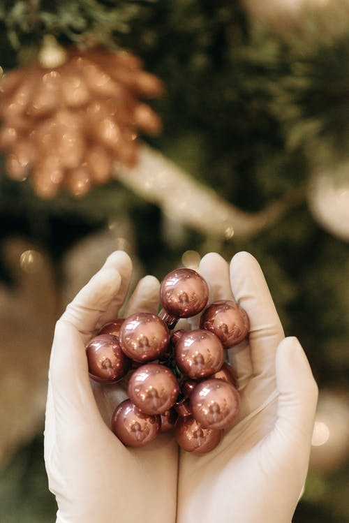 Person Wearing Glove Holding Christmas Balls