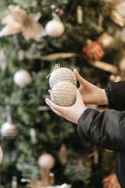 Person Holding White and Brown Round Ornament