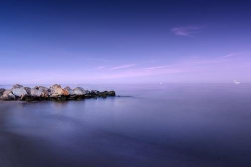 Calm sea with stones on shore