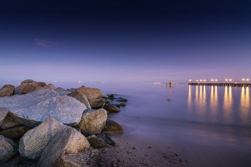 Picturesque seascape of calm sea with boulders on shore and pier on background in evening time in summer