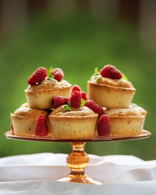 Delicious homemade cake decorated with raspberries and placed on table with white tablecloth