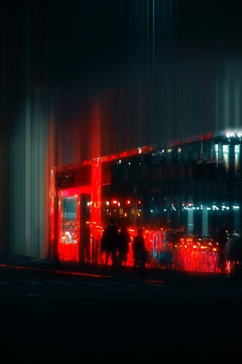 Faceless people on night street near illuminated building