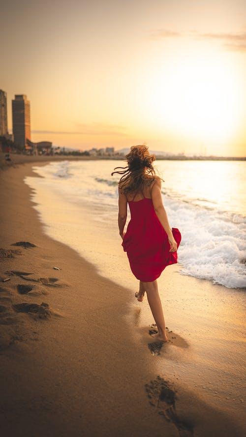 Back view of anonymous female in summer dress strolling on sandy beach near waving ocean under bright sunlight