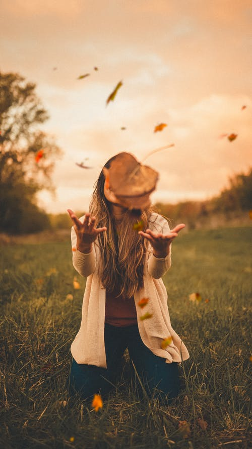Anonymous woman in autumn countryside at sundown