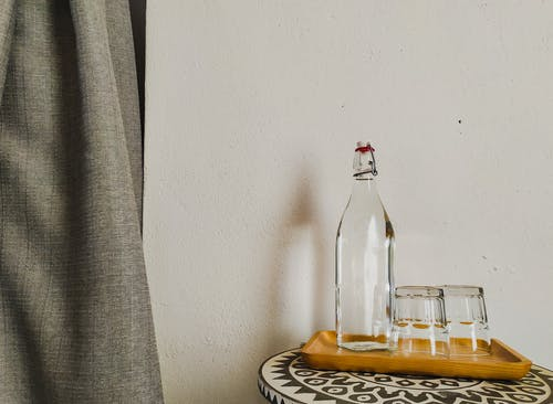 Clear Glass Bottle on White and Black Table