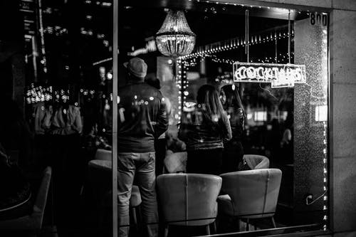 Black and white of young anonymous people spending time in bar with bright lights at night
