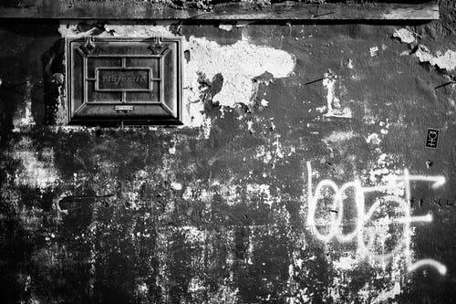 Black and white of aged wall with cracked stucco and graffiti with letters