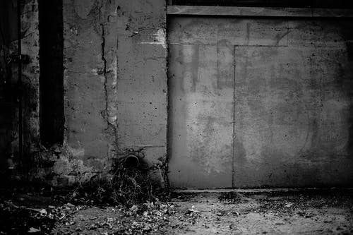 Black and white of aged weathered wall with cracked stucco of forgotten gloomy building