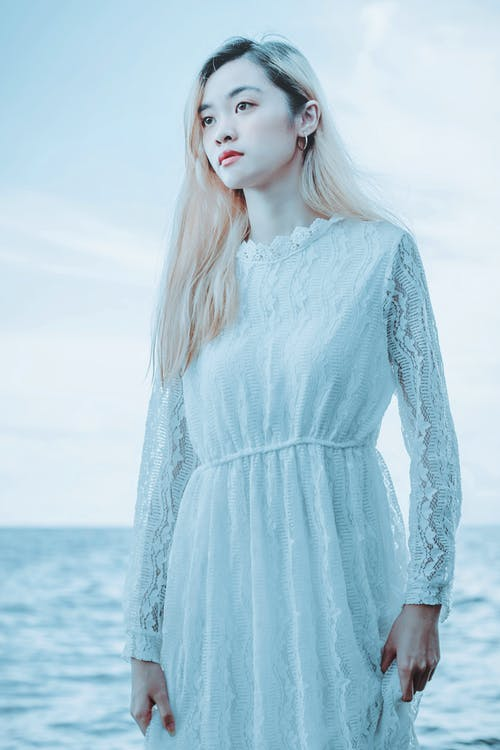 Gentle woman standing on seashore