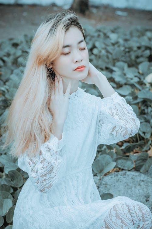 Dreamy woman against green plants