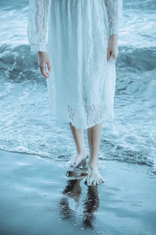 Crop woman on wet sandy shore