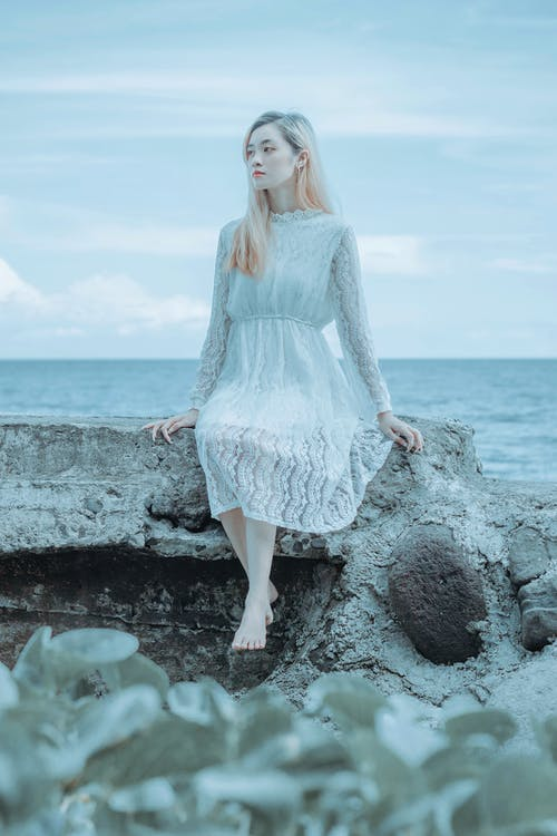 Full body young pensive barefoot Asian female in white dress sitting on shabby concrete pier and looking away