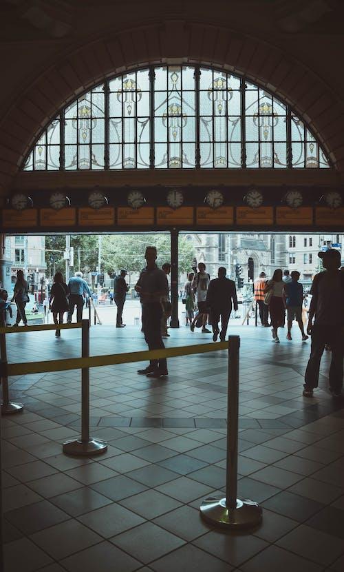 People Walking on White Floor Tiles