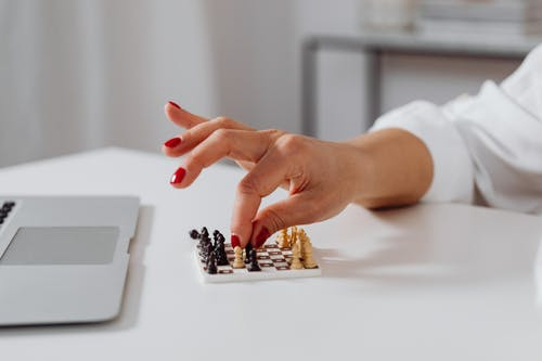 A Person Playing Miniature Chess Toy