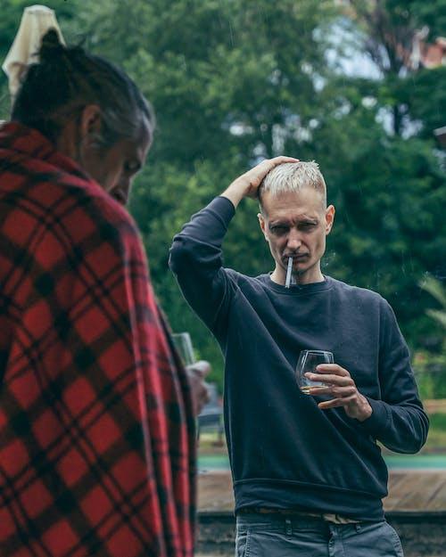 Man in Blue Sweater Smoking Cigarette