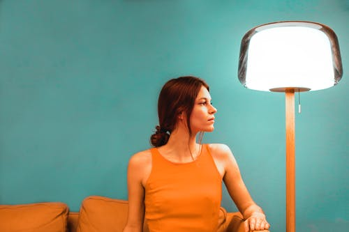 Side view of pensive female sitting on orange couch near glowing lamp against green wall in light room during weekend