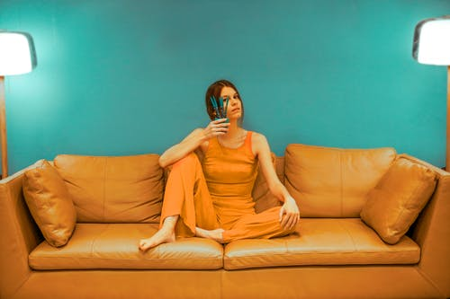 Full body of focused barefoot female wearing casual clothes sitting with bent leg and pot with flower near face on sofa near green wall in room