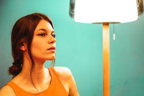 Dreamy woman sitting near lamp