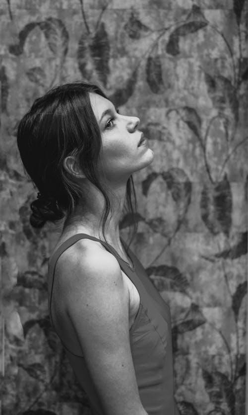 Thoughtful woman standing near wall