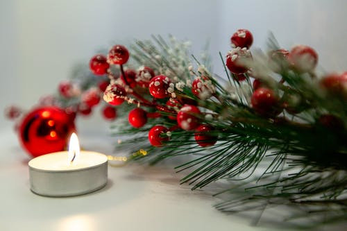 Festive artificial fir twig with Christmas bauble placed on white table near burning tealight on Christmas Eve
