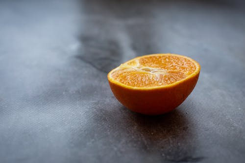 Half of ripe juicy orange placed on black table in kitchen in daylight