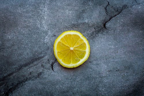 Top view ripe sour lemon slice placed on dark gray cracked background in studio