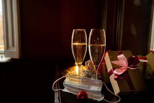 Composition of sparkling champagne glasses placed on table near wrapped gift boxes and protective face mask on Christmas Eve